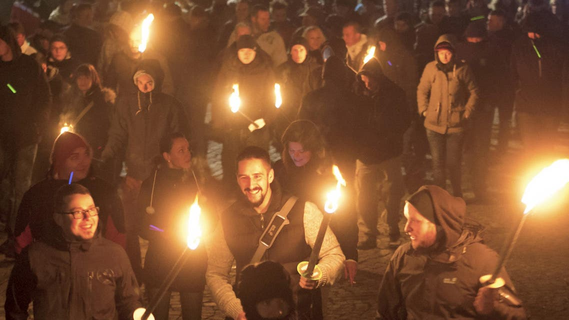 People demonstrate with torches during a rally against a refugee camp with immigrants and asylum-seekers initiated by NPD (National Democratic Party of Germany) in Schneeberg, eastern Germany, Saturday, Nov. 16, 2013. (AP)