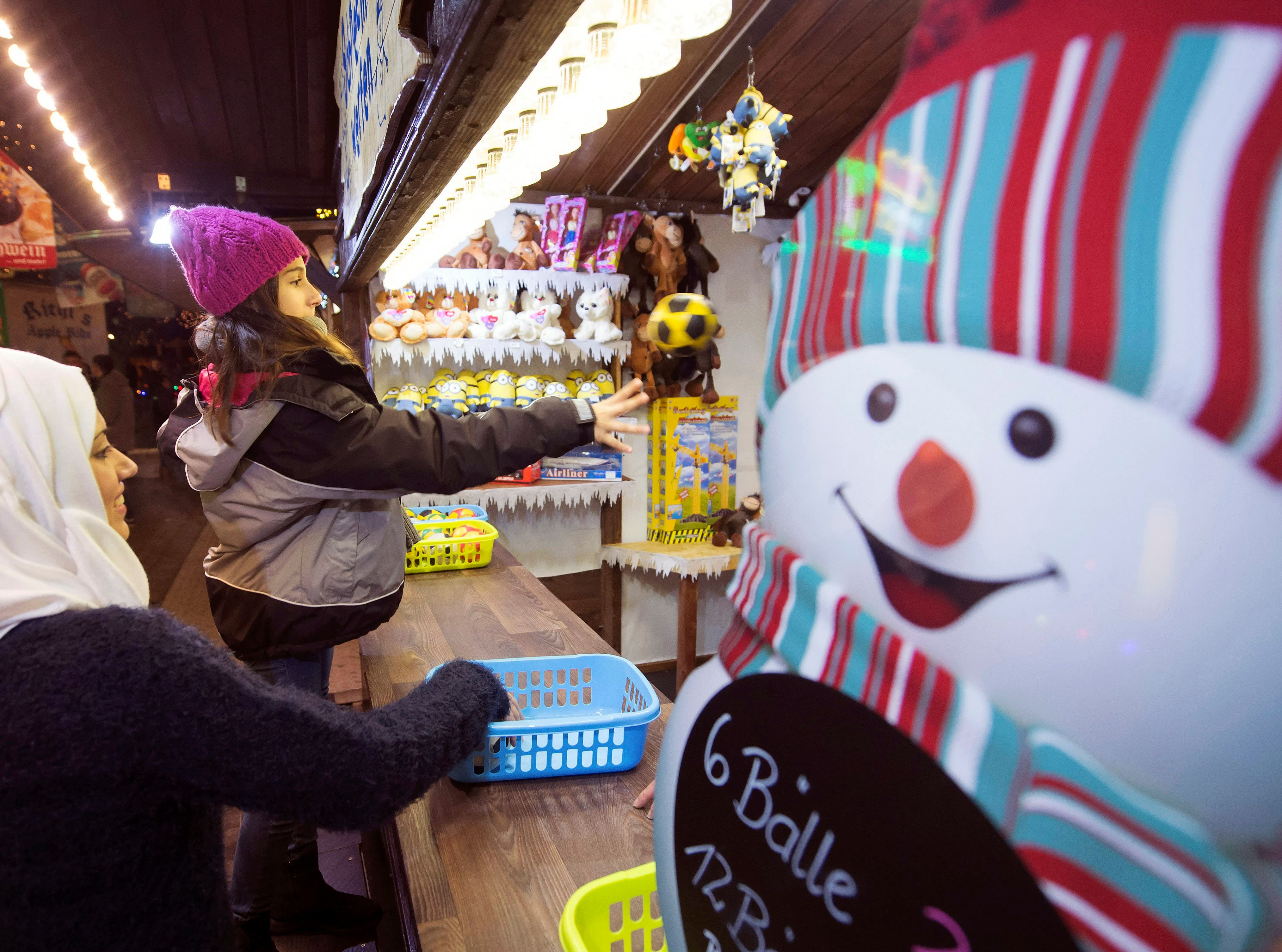 In this photo taken Tuesday, Dec. 8, 2015, Syrian refugee Raghad Habashieh, right, plays a ball besides her sister Reem Habashieh, left, as they visit the Christmas market in Zwickau, eastern Germany.
