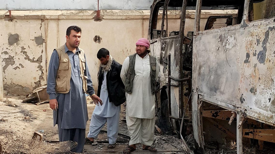 In this Tuesday, Oct. 13, 2015, photo, Afghan businessman Abdul Maroof, left, stands in his warehouse damaged from fighting, in Kunduz, Afghanistan. (AP)