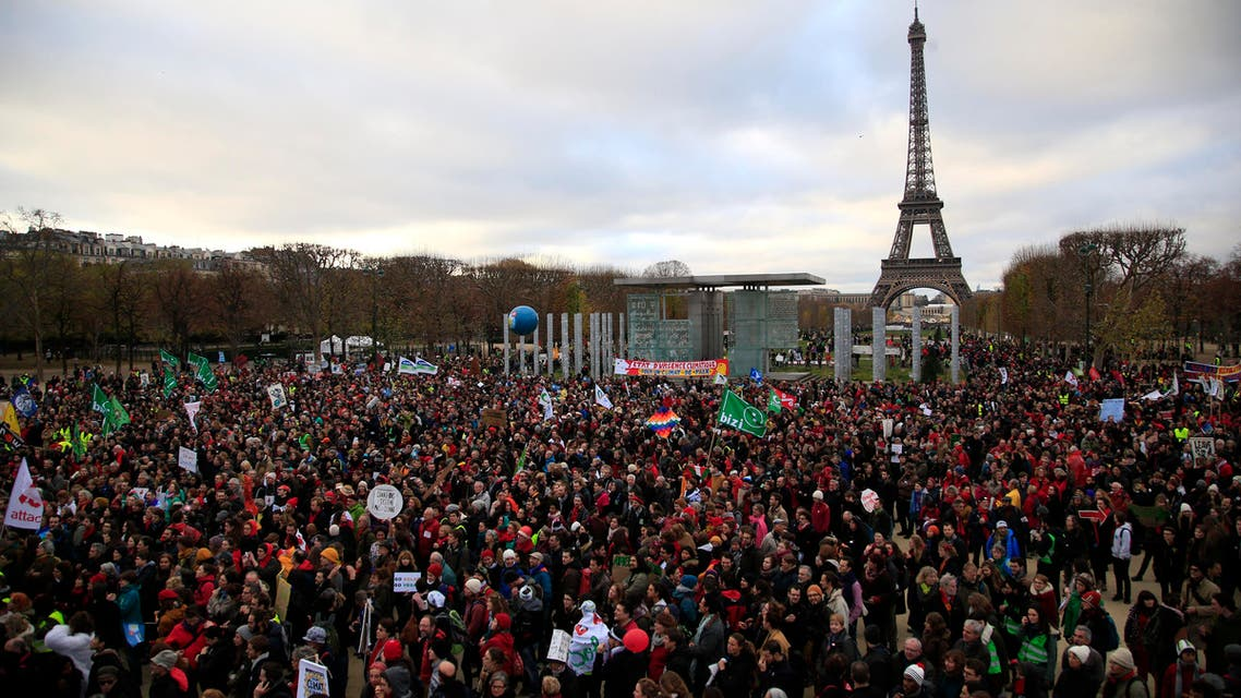 Activists gather near the Eiffel Tower, in Paris, Saturday, Dec.12, 2015 during the COP21, the United Nations Climate Change Conference. As organizers of the Paris climate talks presented what they hope is a final draft of the accord, protesters from environmental and human rights groups gather to call attention to populations threatened by rising seas and increasing droughts and floods. (AP)