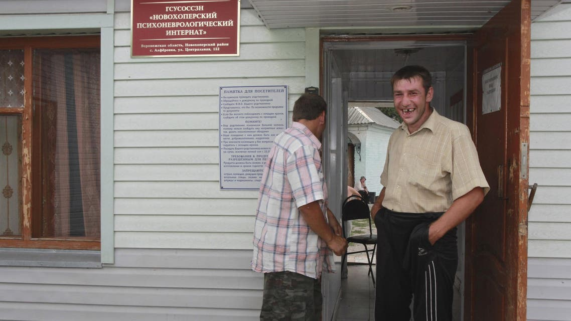 Patients stand near a building of the Novokhopersky Neuropsychiatric Home in the village of Alferovka in the Voronezh region, Russia, July 20, 2011. REUTERS