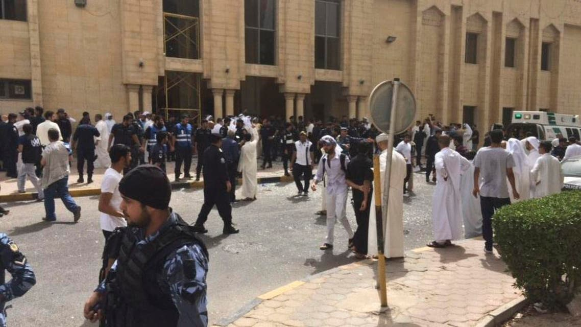 Security forces, officials and civilians gather outside of the Imam Sadiq Mosque after a deadly blast struck after Friday prayers in Kuwait City, Kuwait, Friday, June 26, 2015. There was no immediate claim of responsibility for what appears to be a bombing that targeted the Shiite mosque. (AP