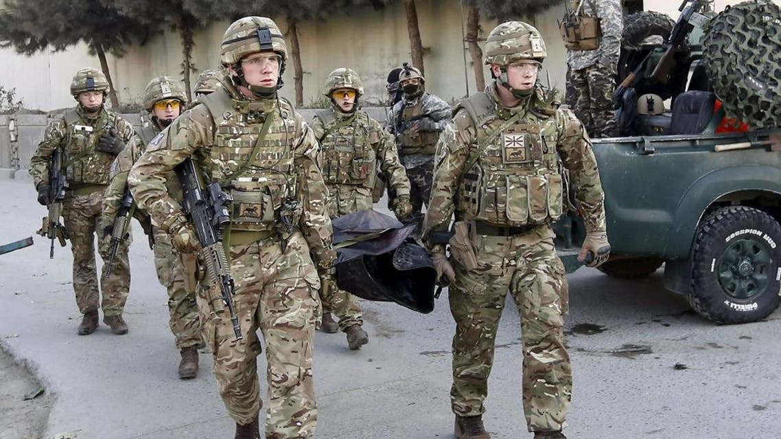 British soldiers carry the dead body of a victim after an attack on a guest house attached to the Spanish embassy in Kabul, Afghanistan December 12, 2015 (Reuters)