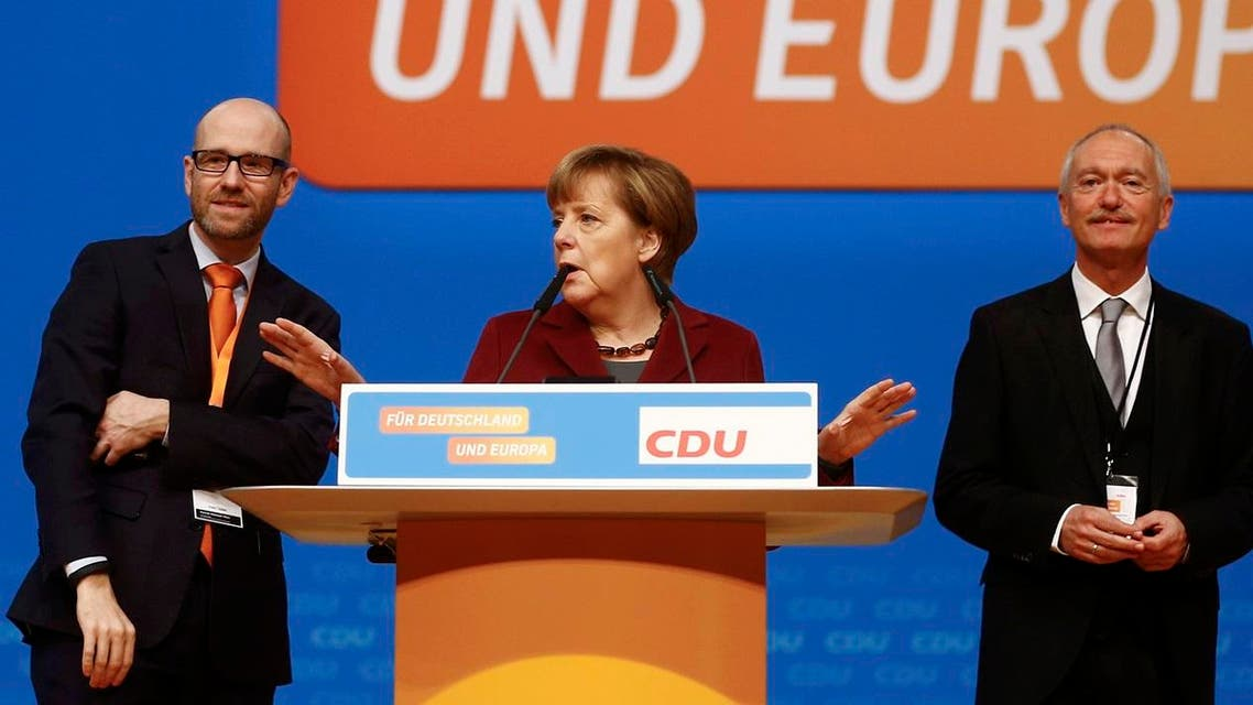 Germany's CDU secretary general Tauber stands on stage with Chancellor Merkel and CDU managing director Schueler as they tour the venue in Karlsruhe. (Reuters)
