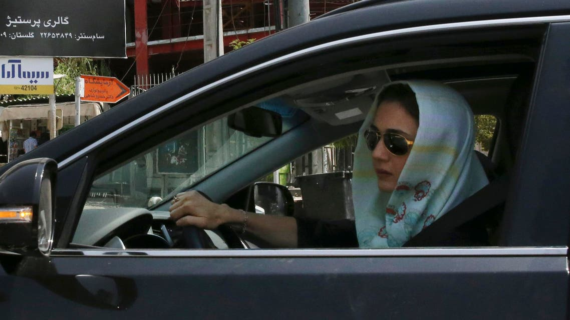 A woman drives in front of an advertising billboard for Bulgari watches in northern Tehran, Iran, Saturday, July 18, 2015. (AP)