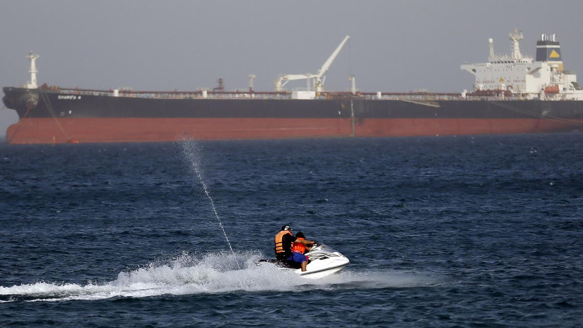 """A couple rides a jetski past the Egyptian crude oil tanker """"Sharifa 4"""" near the beach in El Ain El Sokhna port in Suez before the tanker enters the Suez Canal, east of Cairo, Egypt, July 26, 2015.  (Reuters)"""