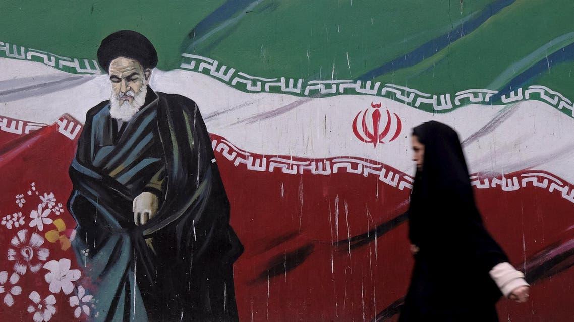 A woman walks past a painting of Iran's late leader Ayatollah Ruhollah Khomeini in Tehran December 11, 2015. (Reuters)