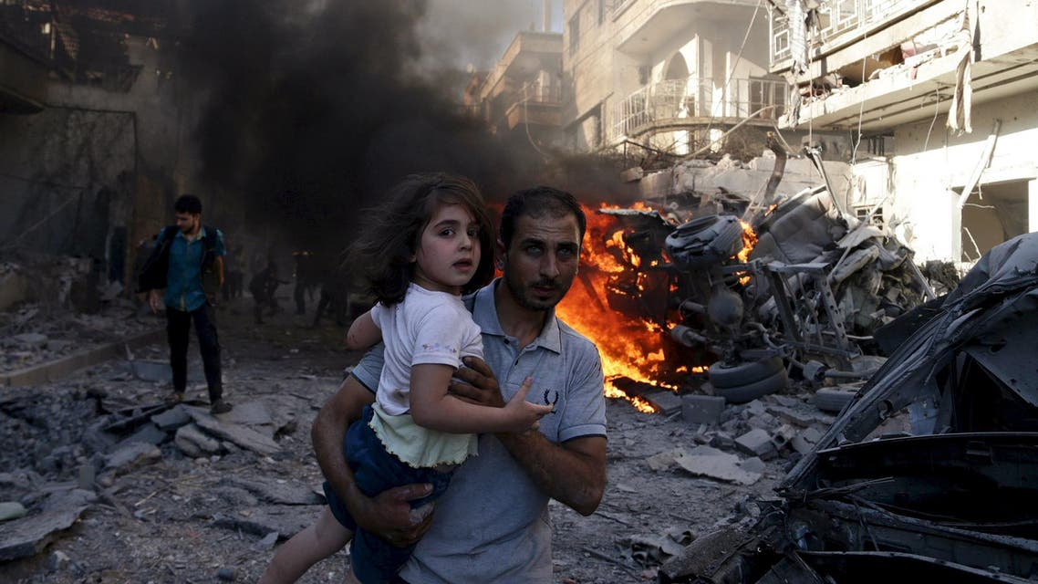 A man carries a girl as they rush away from a site hit by what activists said were airstrikes by forces loyal to Syria's President Bashar al-Assad in the Douma neighbourhood of Damascus, Syria August 24, 2015. (Reuters)
