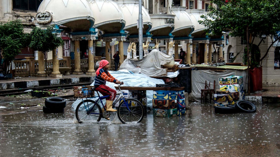 A girl rides a bike during a rain and hail storm, in Alexandria, Egypt, Wednesday, Nov. 4, 2015. (AP)