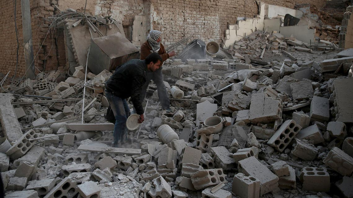 Men search for belongings at a site hit by missiles in the Douma neighborhood of Damascus, Syria December 13, 2015.