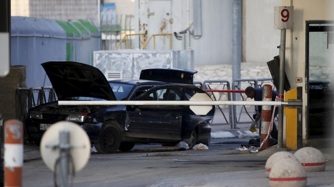 Israeli police forensic experts examine a car used by a Palestinian man in what an Israeli police spokesman said was a car ramming attack at the Qalandiya checkpoint between Jerusalem and the West Bank, December 18, 2015 (Reuters)
