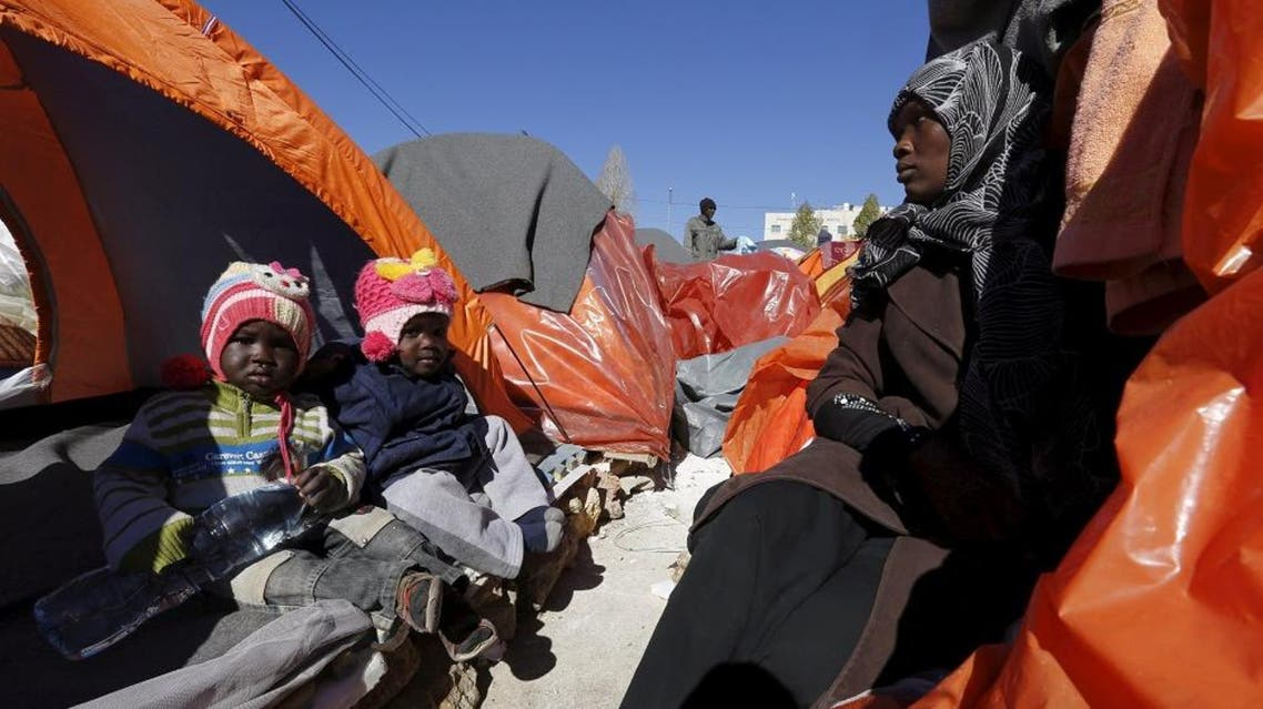 A Sudanese refugee from Darfur sits with her children during an open-ended sit-in outside the United Nations High Commissioner for Refugees (UNHCR) in Amman, Jordan, December 6, 2015 (Reuters)