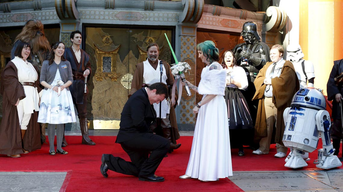 Andrew Porters kneels in front of Caroline Ritter from Australia during their wedding ceremony accompanied by people dressed as characters from Star Wars in the forecourt of the TCL Chinese Theatre in Hollywood, California December 17, 2015.
