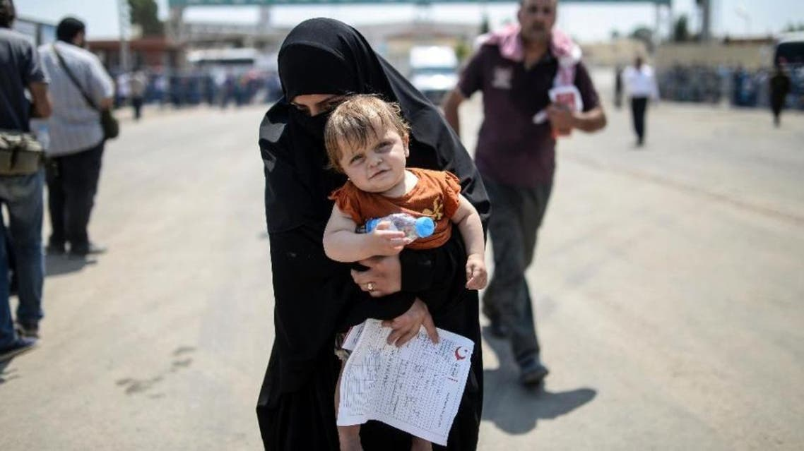 A Syrian woman and her baby arrive in Turkey via the Akcakale border crossing on June 15, 2015; Syria ended visa-free travel by Turks December 17, after Turkey imposed similar restrictions -- though refugees and asylum seekers remain exempt (AFP)