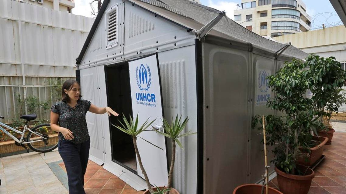 Roberta Russo, a communication officer for the UNHCR, shows a new a pre-fabricated house is to serve as an alternative to tents for refugees that designed by the Swedish furniture manufacturer IKEA. (File: AP)
