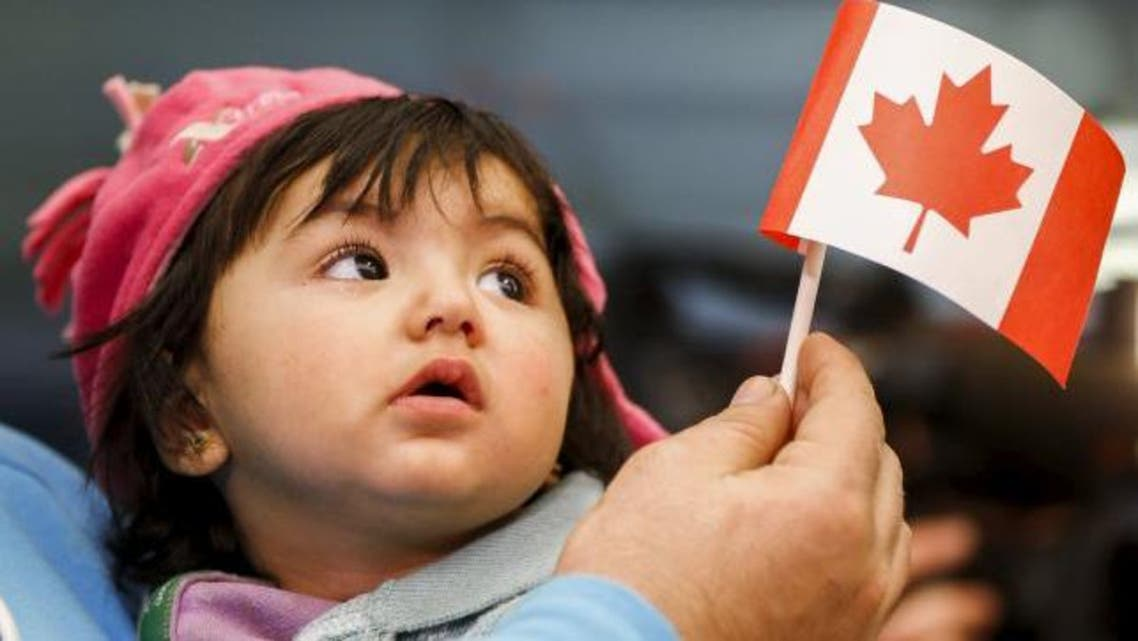 A young Syrian refugee looks up as her father holds her and a Canadian flag at the as they arrive at Pearson Toronto International Airport in Mississauga, Ontario, December 18, 2015. (Reuters)