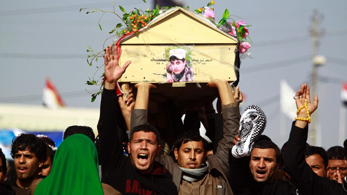 Iraqi mourners carry the body of one of the soldiers who were killed the previous day in a so-called friendly fire from a US-led coalition aircraft west of Baghdad, on December 19, 2015 during a funeral in the Shiite holy city of Najaf. (AFP)