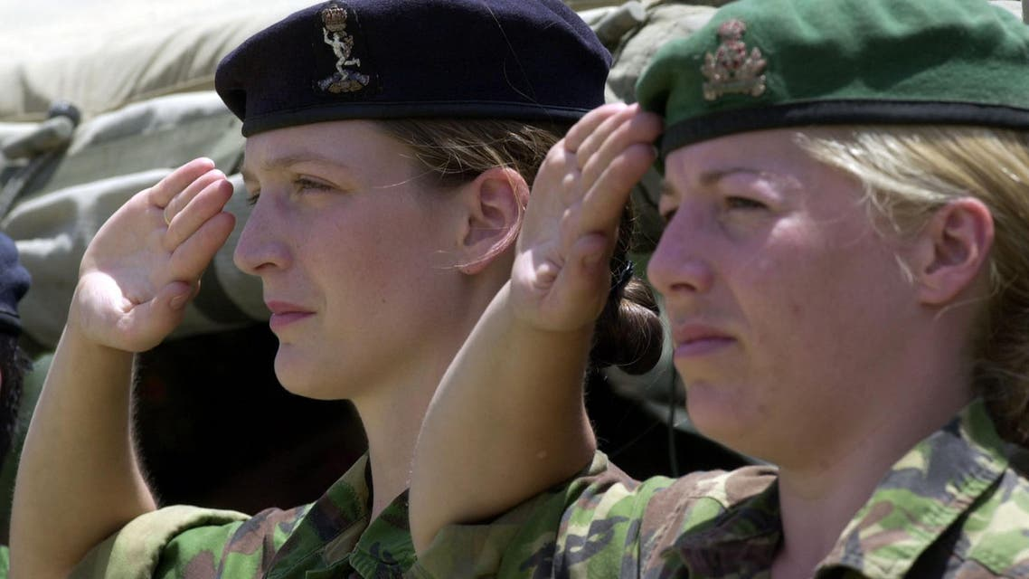 Two British female soldiers salute as they listen to Afghan national anthem during a handover ceremony for the command of the International Security Assistance Force, ISAF, Thursday, June 20, 2002.