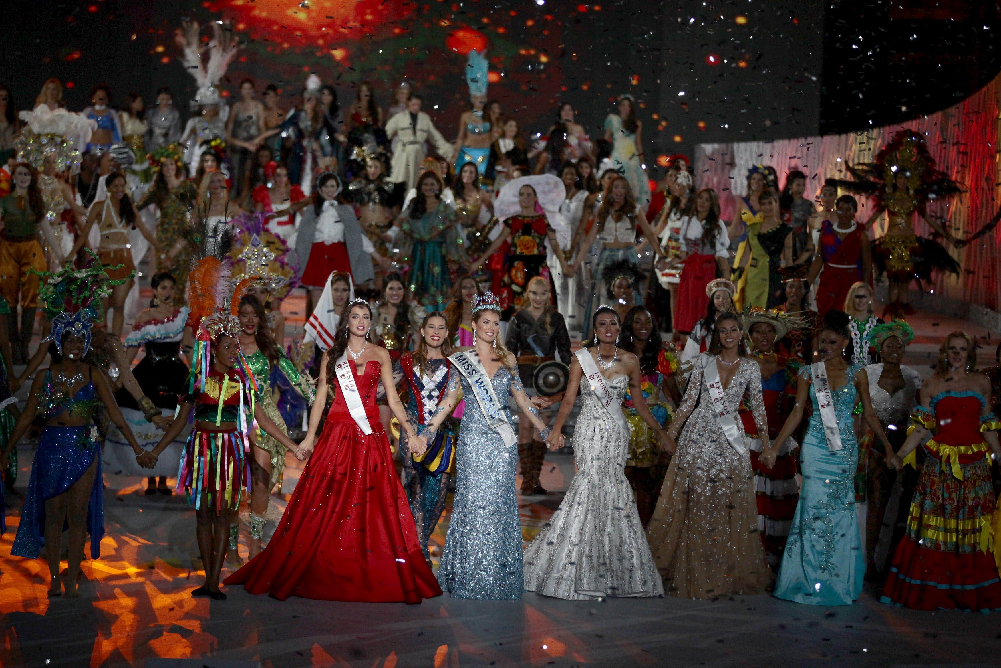 Winner of Miss World 2015 Miss Spain Lalaguna Royo holds hands with other contestants during the pageant in Sanya