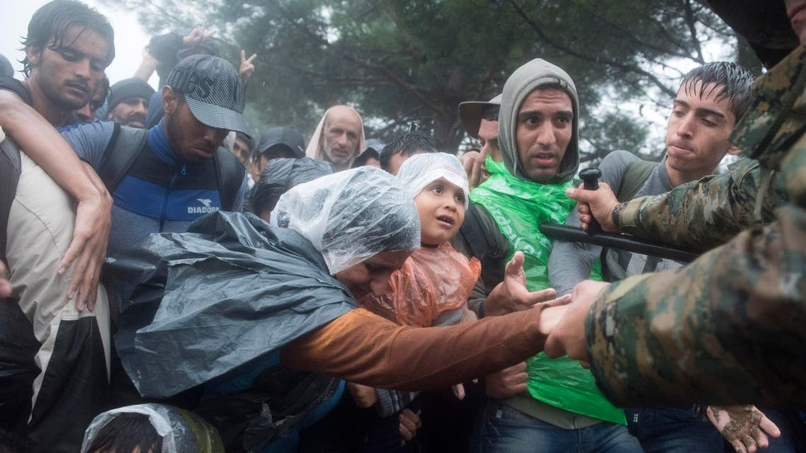 n this photo taken on Thursday, Sept. 10, 2015, Macedonian border police helps refugees and migrants to pass in heavy rainfall from the northern Greek village of Idomeni to southern Macedonia. (AP)
