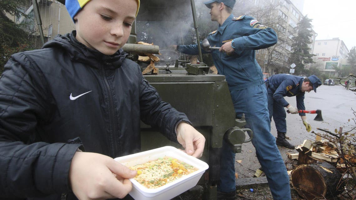 boy carries a container with soup as he visits a mobile station, opened and operated by members of the Russian Emergencies Ministry to lend support and to distribute hot meals among local residents due to power cuts in the settlement of Massandra, Crimea, November 27, 2015.