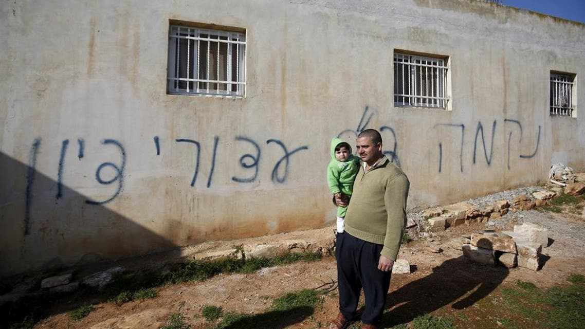 A Palestinian man holds his son as he stands in front of Hebrew graffiti sprayed on the wall of a Palestinian home in what Israeli police believe was an attack by Jewish militants in the village of Beitillu near the West Bank city of Ramallah December 22, 2015. (Reuters)