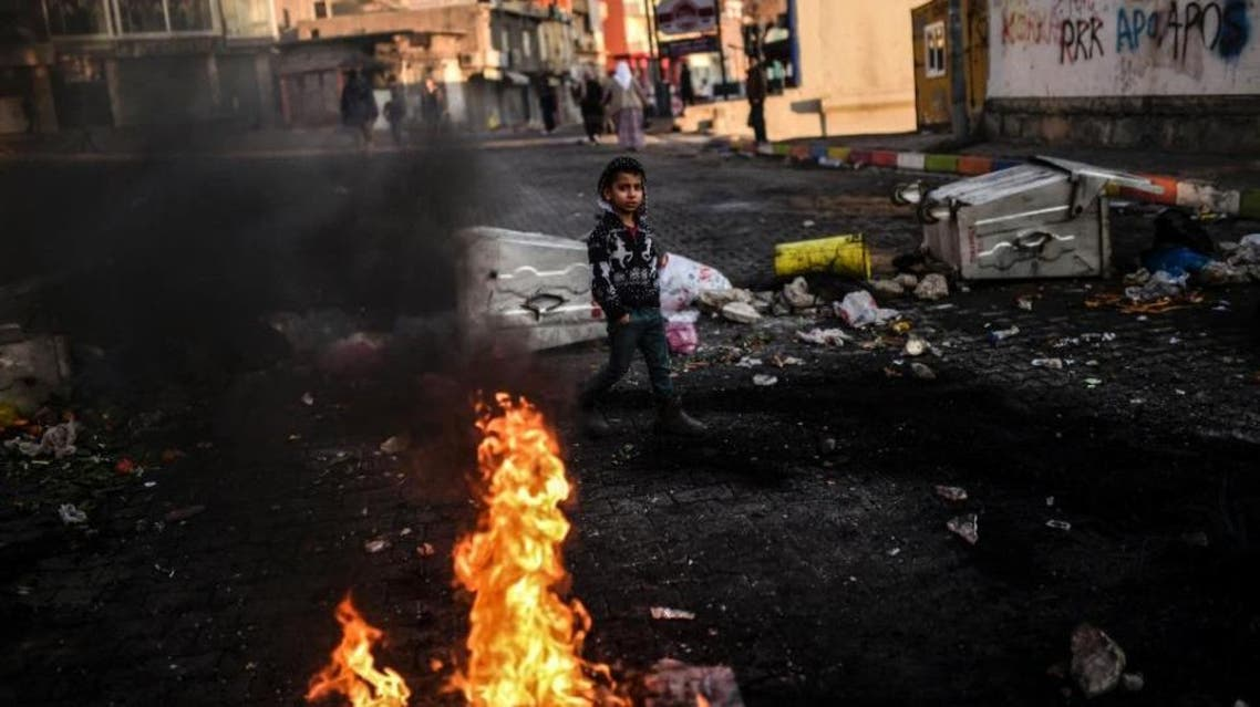 A Kurdish boy makes his way past a barricade during a protest of security operations targeting Kurdish rebels in the southeastern Turkish cities Cizre and Silopi. (AFP)