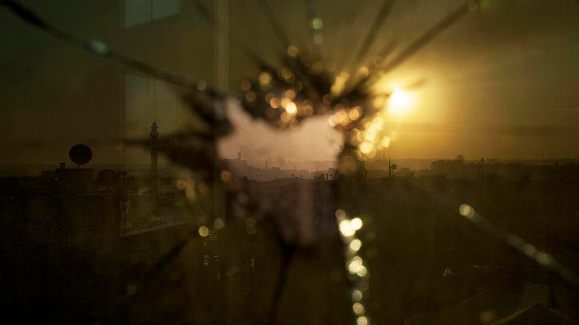In this Saturday, Oct. 13, 2012 photo, smoke rises from buildings due to government forces shelling seen through broken glass in Aleppo, Syria. (File photo: AP)