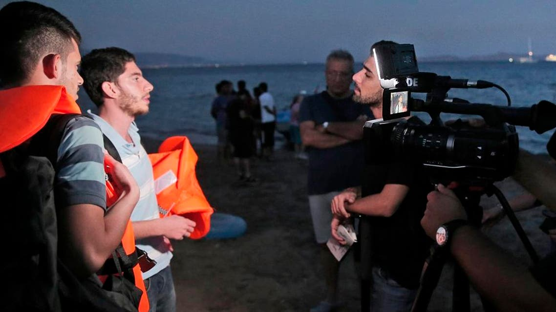 FILE - In this early Tuesday, Aug. 18, 2015 file photo, freelance translator Mohammed Rasool, centre, working for the Associated Press, interviews refugees ready to board a dinghy to try to cross from near the coastal town of Bodrum Turkey, to the nearby Greek island of Kos. Rasool, a 24-year-old Iraqi Kurd who has worked as a fixer for The Associated Press, was helping two Vice News reporters covering clashes between the PKK's youth group and police. He was arrested on Aug. 27 and remains in a maximum security prison in Turkey. Vice Media is carrying out a two-hour blackout on its websites to call attention to an Iraqi Kurdish journalist who has been held in Turkish jails without charges since being arrested while working for the news organization.(AP Photo)