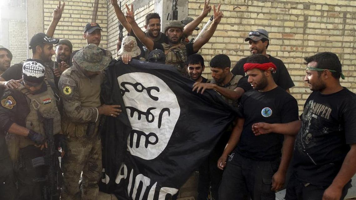 Iraqi security forces stand with an Islamist State flag which they pulled down at the University of Anbar, in Anbar province July 26, 2015 (Reuters)