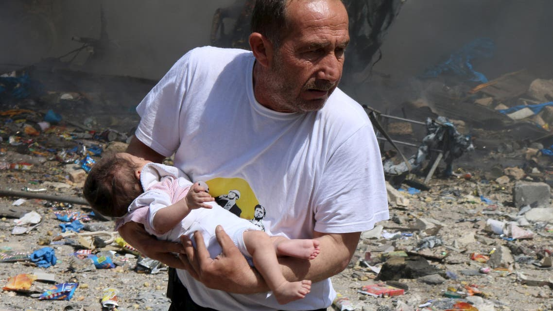 A man holds a baby that survived what activists said was a site hit by a barrel bomb dropped by forces loyal to Syrian President Bashar al-Assad at the old city of Aleppo June 3, 2015. (Reuters)