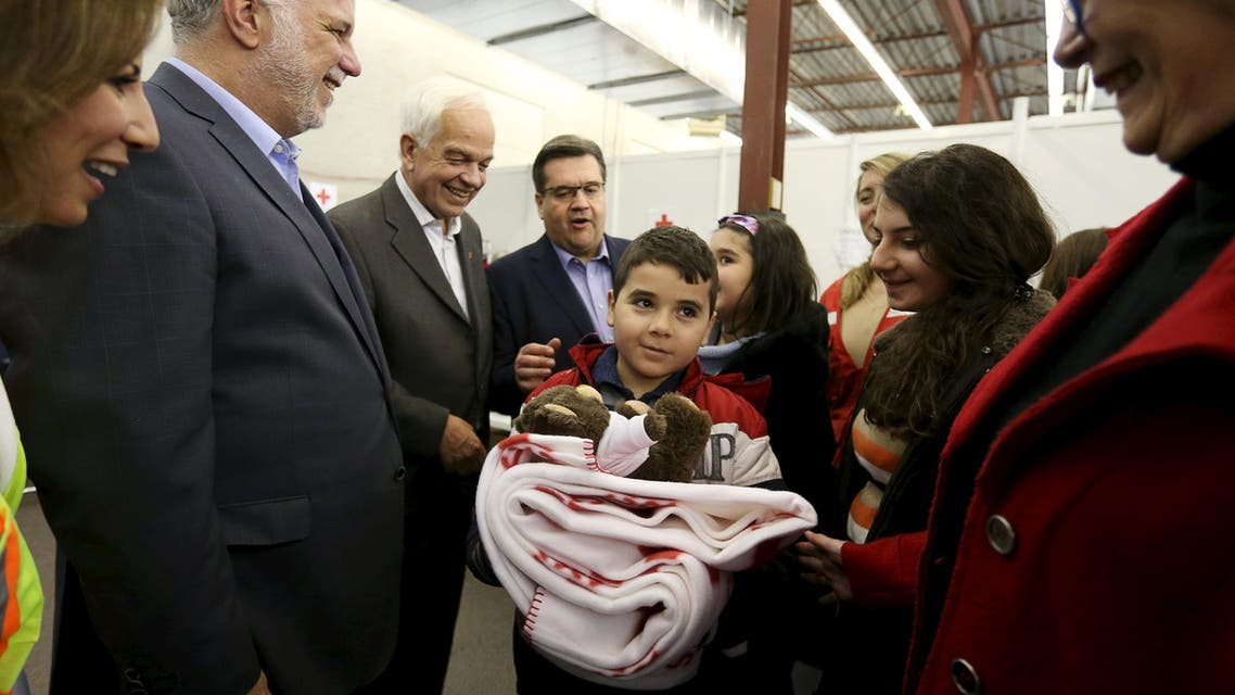 A Syrian refugee family is greeted by Quebec Premier Philippe Couillard (2nd L), Canada's Immigration Minister John McCallum (3rd L) and Montreal Mayor Denis Coderre (C) at the Welcome Centre in Montreal, Quebec, December 12, 2015. REUTERS