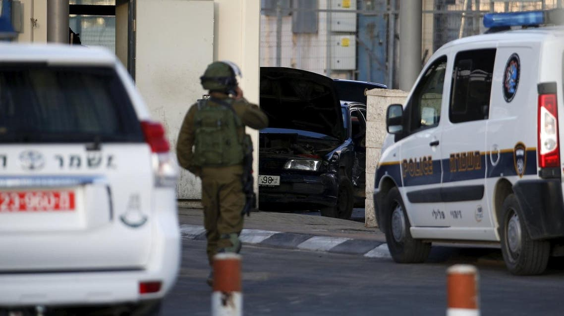 An Israeli soldier stands in front of a car (C) used by a Palestinian man in what an Israeli police spokesman said was a car ramming attack at the Qalandiya checkpoint between Jerusalem and the West Bank, December 18, 2015. (Reuters)