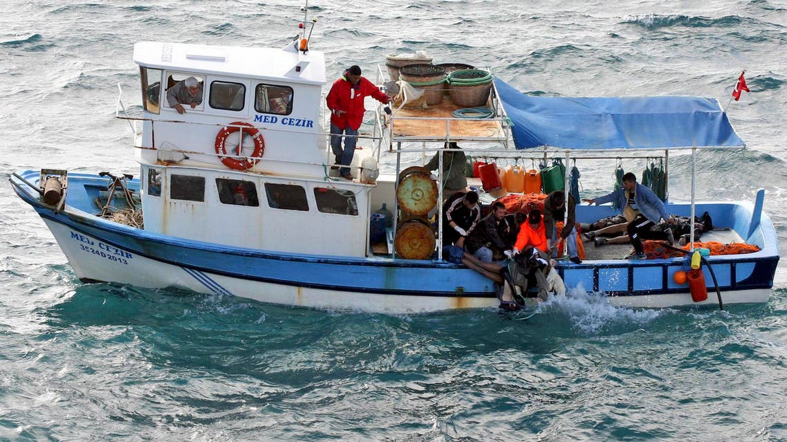 A Turkish coast guard and fishermen pull bodies of illegal migrants from the sea off the Aegean port city of Izmir, western Turkey, Monday, Dec. 10, 2007.