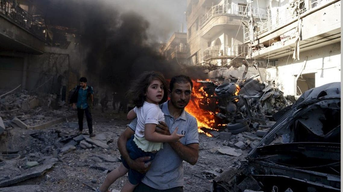 A man carries a girl as they rush away from a site hit by what activists said were airstrikes by forces loyal to Syria's President Bashar al-Assad in the Douma neighbourhood of Damascus, Syria August 24, 2015