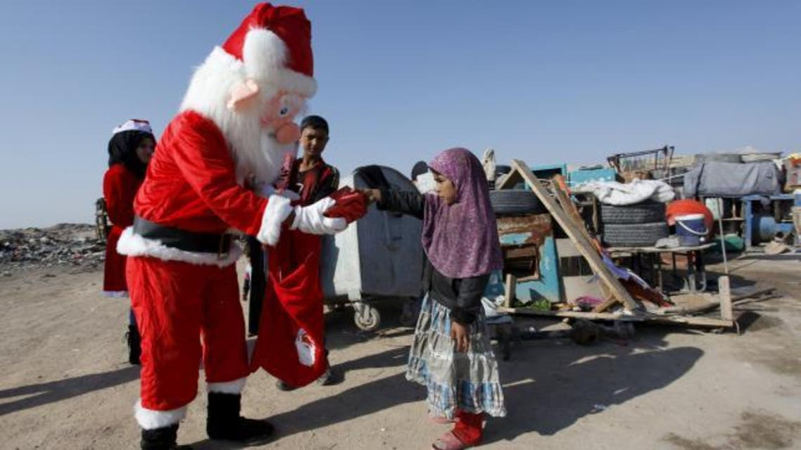 A volunteer wearing a Santa Claus costume distributes presents to children at a poor community in Najaf, south of Baghdad, December 19, 2015.