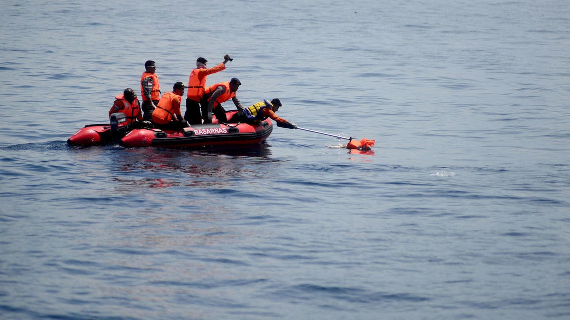 Indonesian search and rescue team members gather the dead body of a baby during an operation in the Sulawesi sea, near Kolaka city on December 24, 2015.