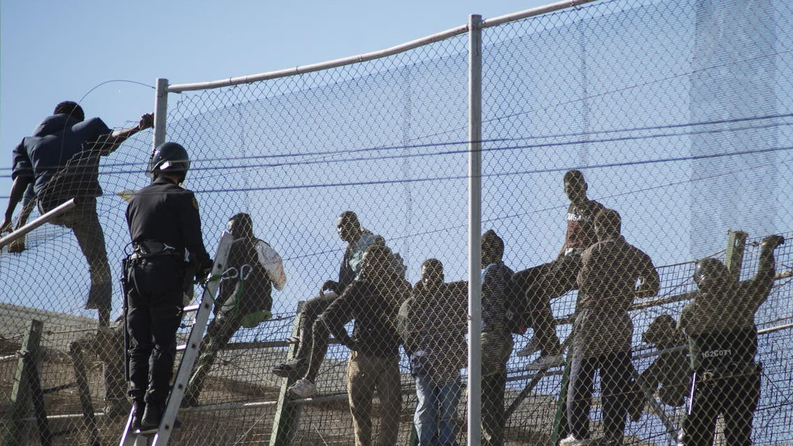 African migrants sit on top of a border fence during an attempt to cross into Spanish territories, between Morocco and Spain's north African enclave of Melilla, November 21, 2015. (Reuters)