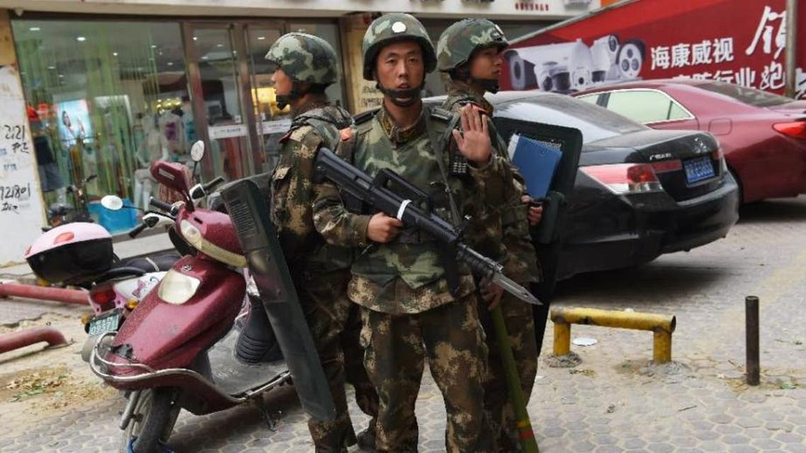 Paramilitary police are seen standing guard outside a shopping mall in Hotan, China's western Xinjiang region (AFP Photo/Greg Baker)