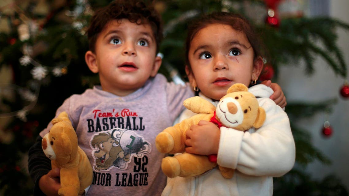 Two-year old twins Hevedar and Heve of Iraq pose in front of a Christmas tree at a refugee shelter in an evangelic church in Oberhausen. (Reuters)