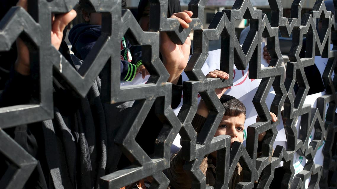 A Palestinian boy looks through the gate of Rafah border crossing during a rally calling on Egyptian authorities to open the crossing, in Rafah in the southern Gaza Strip December 22, 2015. REUTERS