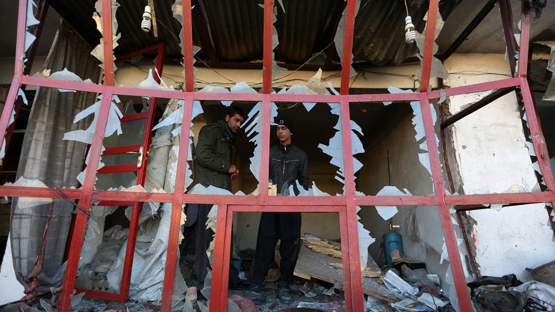 Afghan shopkeeper watches from a broken window of his shop near the site of suicide car bomb attack in Kabul, Afghanistan, Monday, Dec. 28, 2015.
