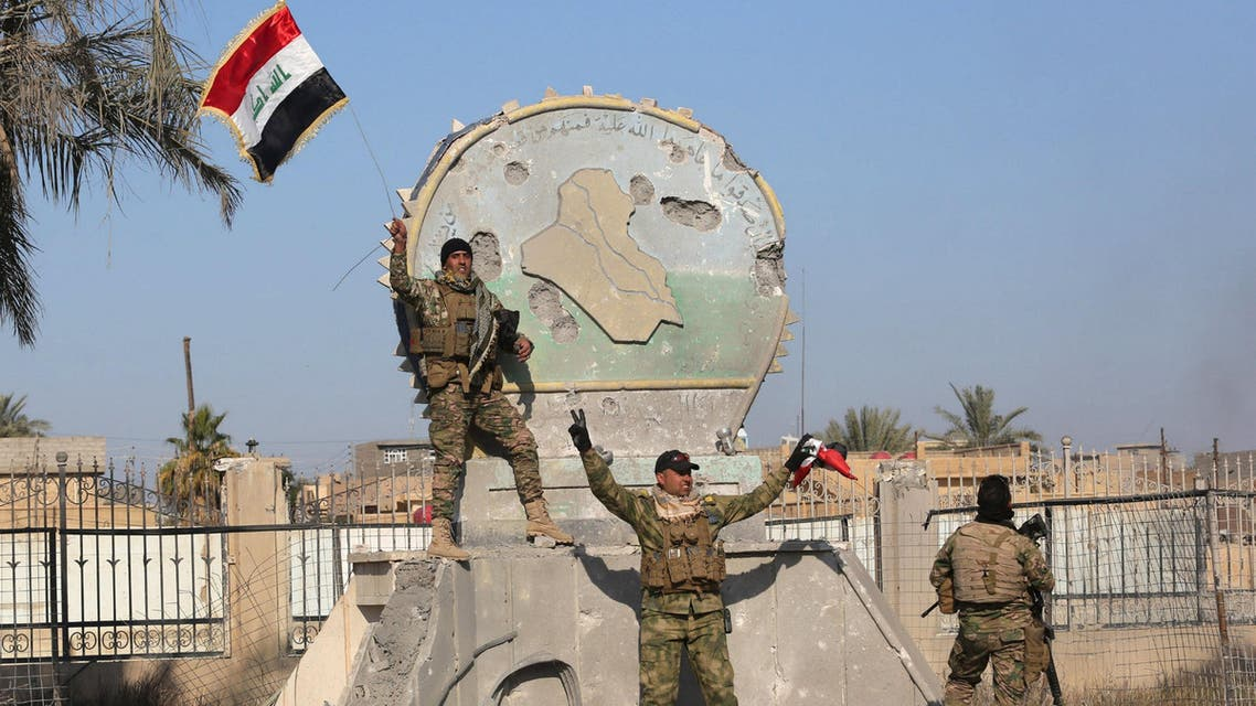A member of the Iraqi security forces holds an Iraqi flag at a government complex in the city of Ramadi, December 28, 2015. (Reuters)