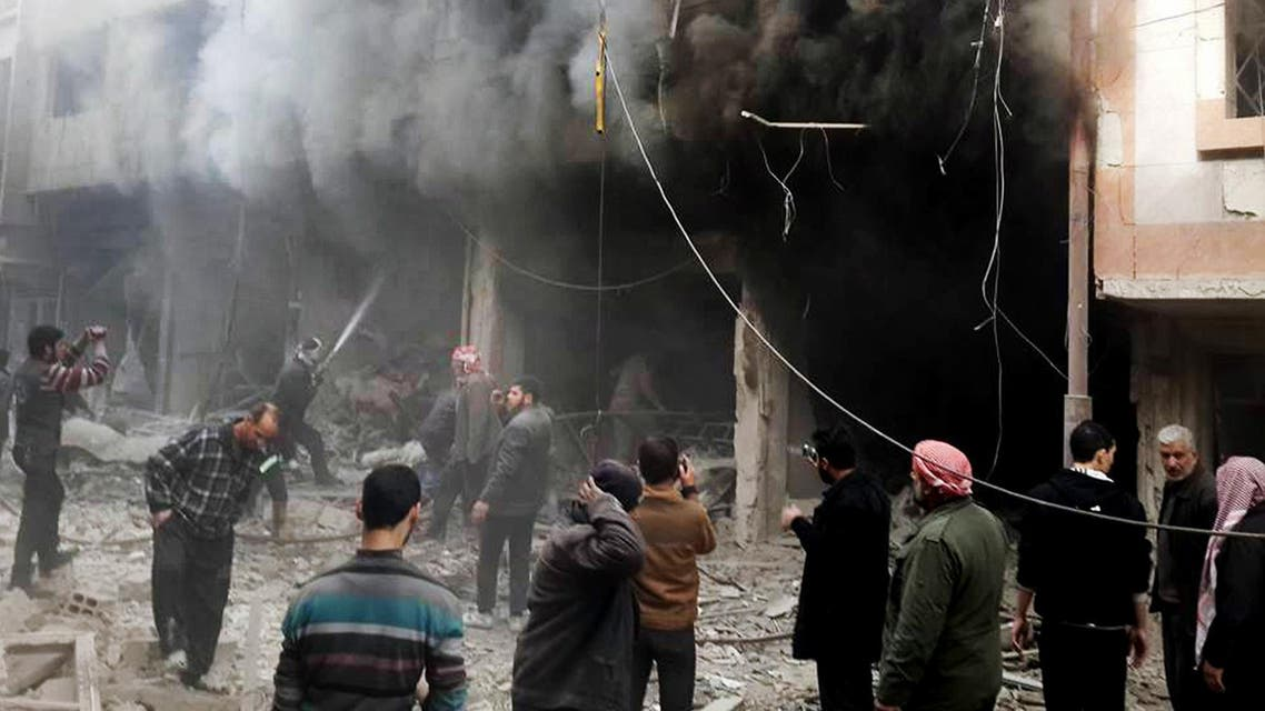 This photo released on Sunday, Dec 13, 2015 by the Douma Revolution News Network on their Facebook page, shows Syrians trying to extinguish fire that was caused by Syrian government aerial bombardment on the Damascus suburb of Douma, Syria. ap