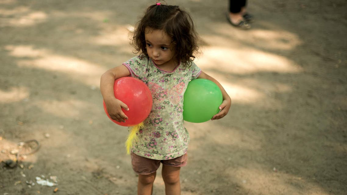 A migrant girl plays with balloons as the newly arrived migrants wait in front of the State Office for Health and Social Affairs to apply for asylum in Berlin, Germany August 11, 2015.
