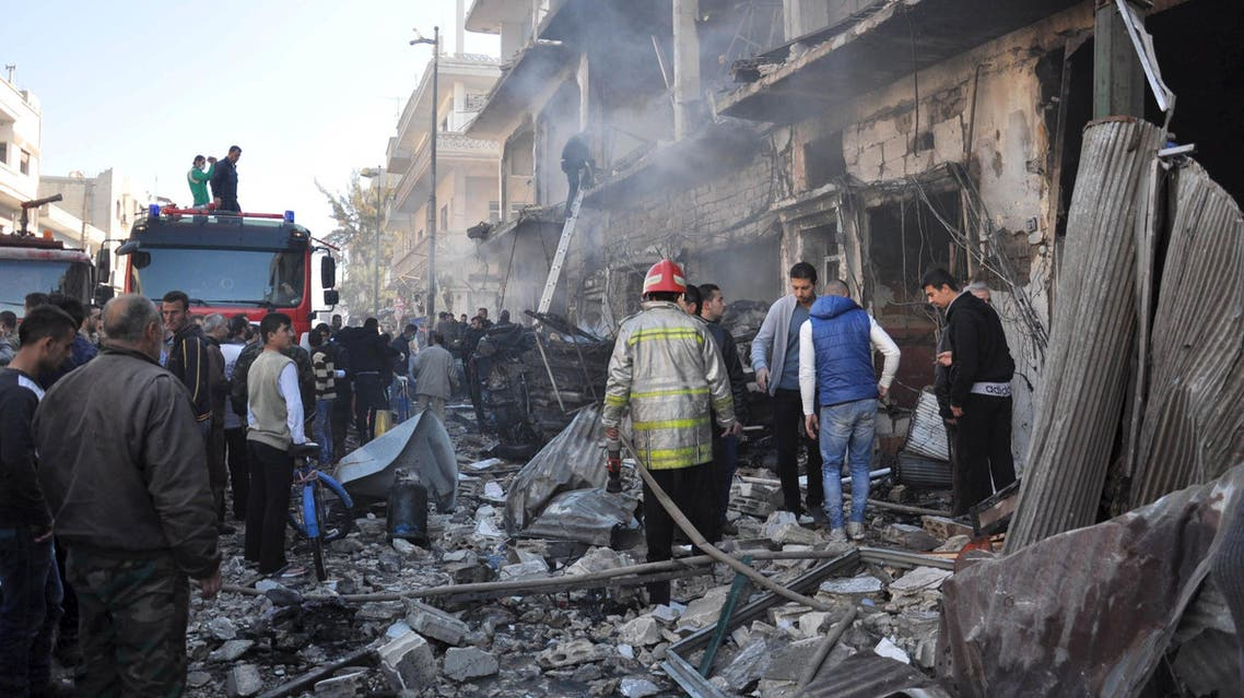 Civil Defence members work at the site of two bomb explosions in the Syrian city of Homs, Syria, in this handout picture provided by SANA on December 28, 2015. (Reuters)