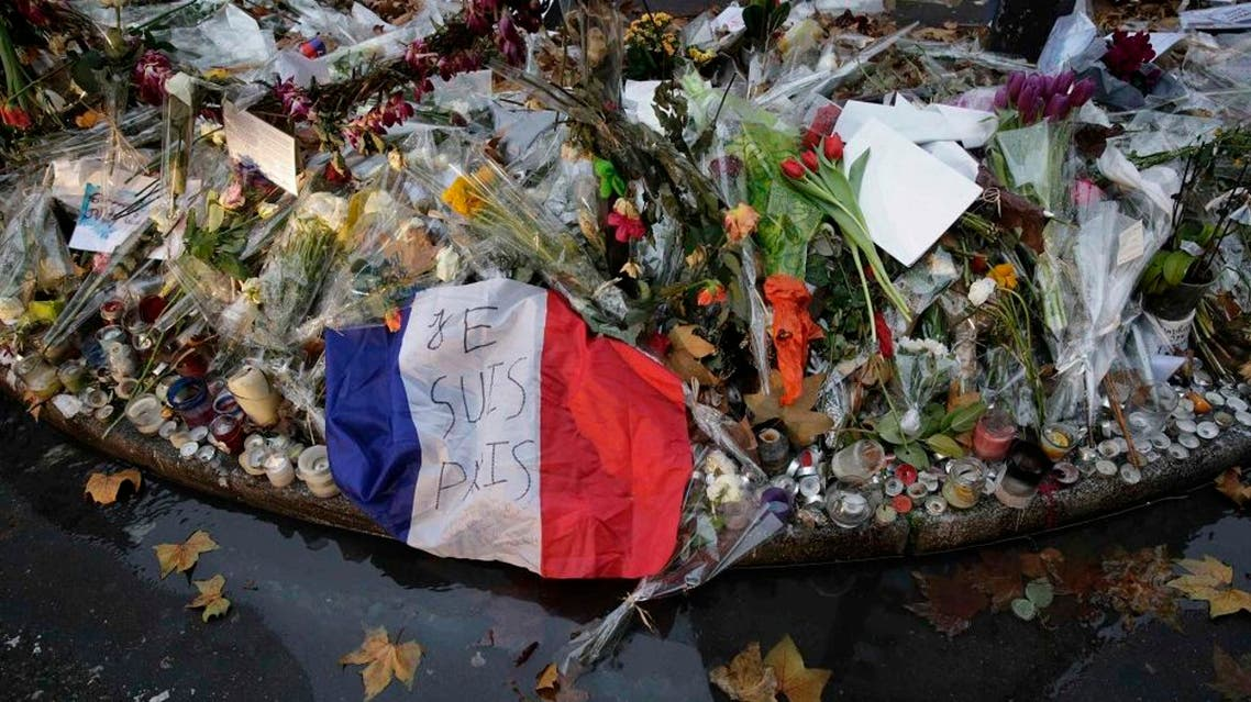 """A French flag with the message """"I am Paris"""" is seen among candles and flowers left by passers-by at an informal memorial in front of the""""Casa Nostra"""" pizzeria, one of the sites of the November shooting attacks, in Paris, France, December 18, 2015 