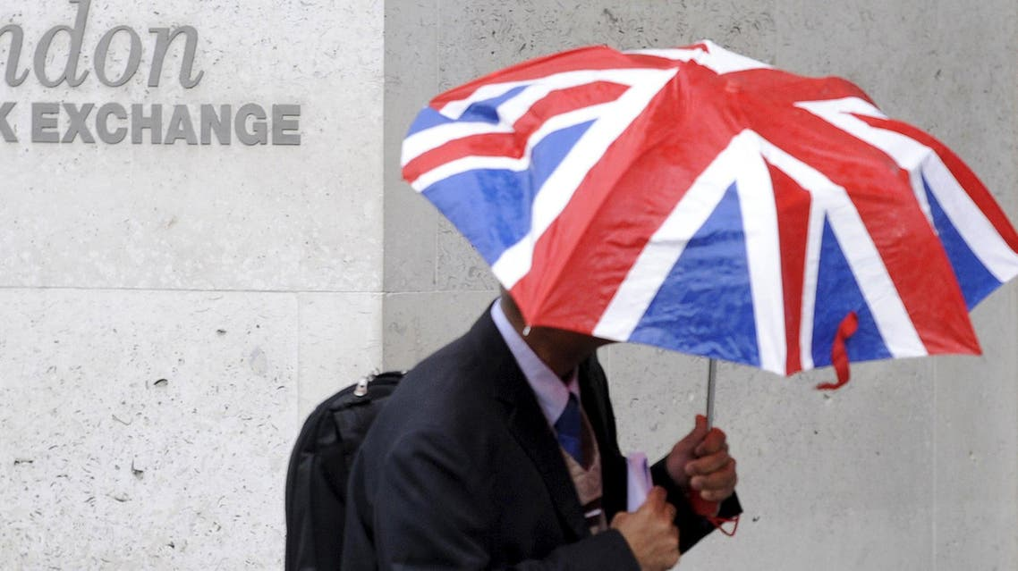 A worker shelters from the rain as he passes the London Stock Exchange in the City of London at lunchtime in this October 1, 2008 file photo.  (Reuters)