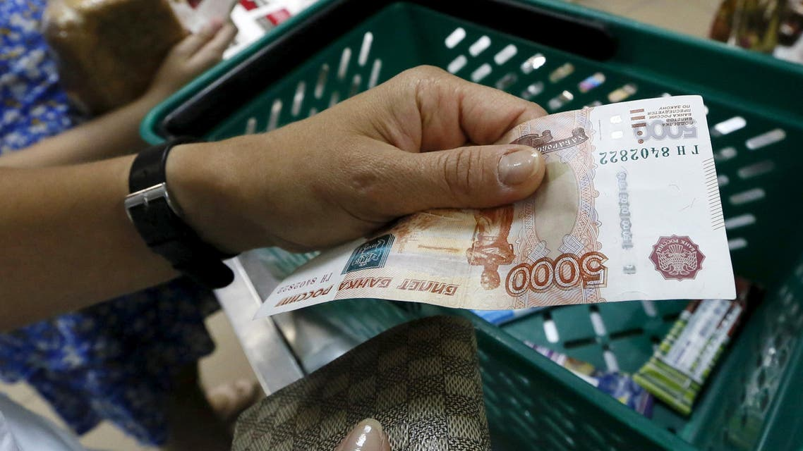 A customer holds a Russian 5,000-rouble as she buys food at a grocery shop in the Siberian city of Krasnoyarsk, Russia, August 6, 2015. (Reuters)