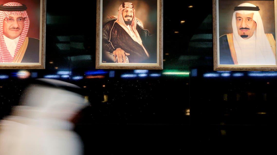 A man walks past portraits of Saudi leaders at the Tadawul Saudi Stock Exchange, in Riyadh, Saudi Arabia, Monday, June 15, 2015. (AP)